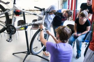 A mechanic adjusts brakes watched by trainees on a maintenance course