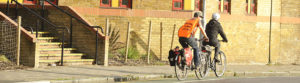 Two riders on an urban road. The front one is a female trainee followed by an instructor in an orange hi-viz jacket