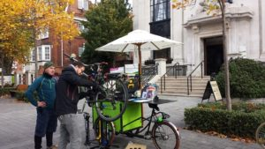 Dr Bike's cargo bike outside the town hall, where a resident is shown how to adjust his bike