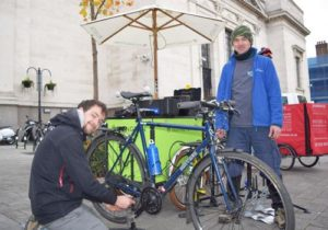 A mechanic and a member of teh public work together to repair a bike outside the town hahh